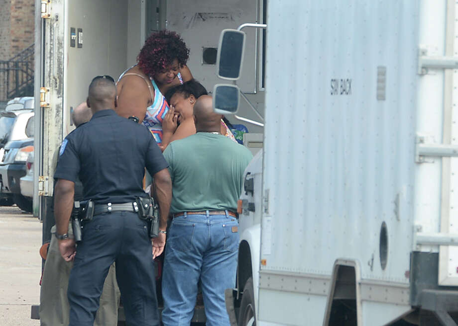 A young woman is comforted by family as she makes her way into a waiting truck after being safely removed from an apartment at the Timber Ridge Apartments complex on Pinchback Road in Beaumont Tuesday. The woman texted her mother late morning that she was being held in the apartment at knifepoint by her alleged boyfriend. Police and members of the SWAT team responded, and the woman was released safely around 3:30 in the afternoon. Shortly later, the suspect was taken into custody. There were no injuries in the incident.  Photo taken Tuesday, September 29, 2015  Photo by Kim Brent / Beaumont Enterprise