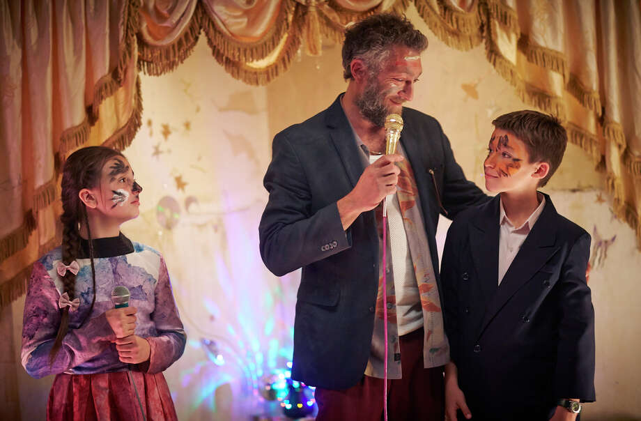 Vincent Cassel (center) plays cult leader Gregori, who celebrates the birthday of Alexander (Jeremy Chabriel, right) but also teaches children to kill. / Warp Films