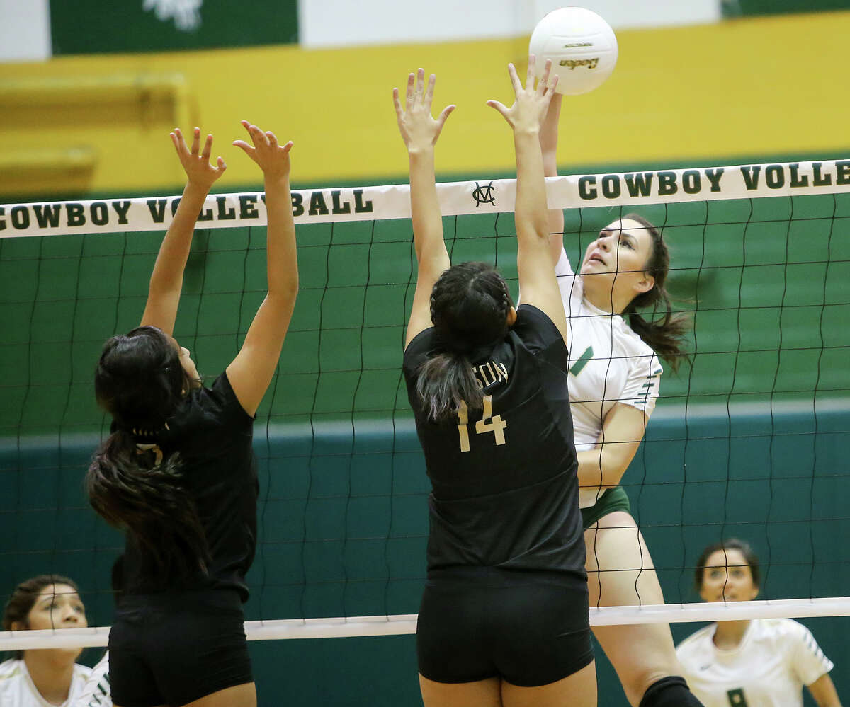 McCollum's Miranda Rich (right) shoots over Edison's Mercedes Padilla (14) and Kamryn Duque during their match at McCollum on Tuesday, Sept. 22, 2015. McCollum beat the Lady Bears in three straight sets: 25-18, 25-20, 25-21. Both teams were undefeated in District 28-5A play with 6-0 records coming into the match. MARVIN PFEIFFER/ mpfeiffer@express-news.net