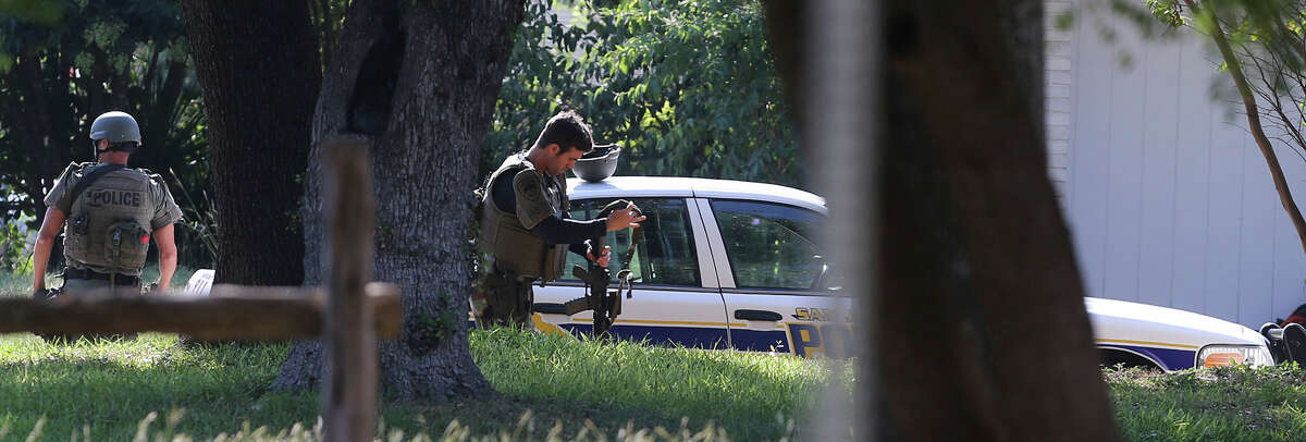 A San Antonio police officer gears up (center) with a rifle Wednesday September 30, 2015 during standoff situation on the 3000 block of Sage Hill. A person at a home in the area has allegedy been firing shots.