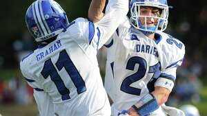 Darien quarterback Tim Graham (11) left, high-fives running back Shelby Grant (21) after Grant scored during the Blue Wave's lopsided win at Greenwich Saturday. Grany scored six touchdowns in the win.