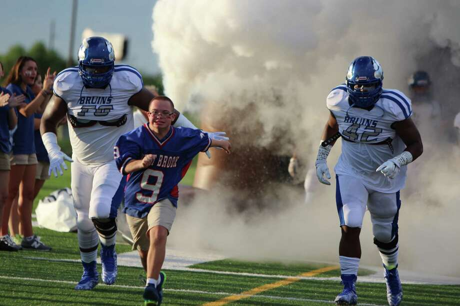 West Brook High School student Michael Littlefield, center, flanked by Alfred Beverly and Chrisian Bluiett, leads the Bruins on the field. Littlefield runs the flag across the end zone after West Brook scores.