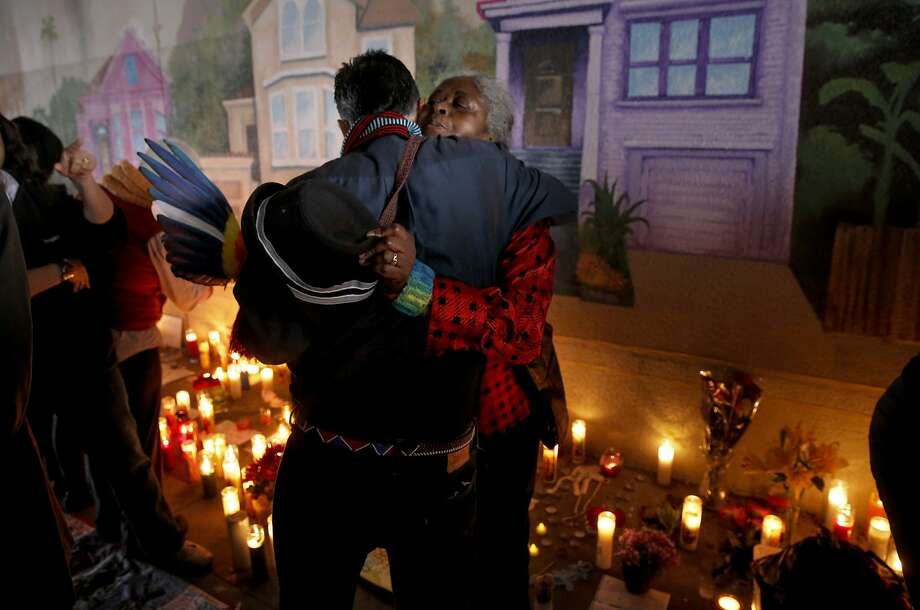 Guillermo Ortiz and Ora Knowell embraces in front of the growing memorial as family, friends and supporters gathered for a candlelight vigil, on Wed. September 30, 2015, to remember artist Antonio Ramos who was shot and killed yesterday while working on a mural on the 3500 block of West St. in Oakland, Calif. Photo: Michael Macor, The Chronicle