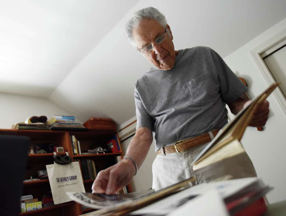 COLLECTING THE PAST City native Lester Sharlac pages through his collection of historic Stamford memorabilia at his home. The cornerstone of his collection is book after book of historic postcards.