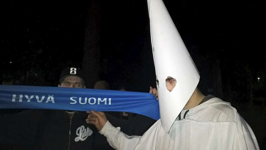 A demonstrator wears a Ku Klux Klan outfit during a protest against refugees in Lahti, Finland. Photo: Markus Luukkonen, AFP / Getty Images