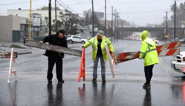 Albany traffic safety officer Mike Romano, left, assists members of the Department of General Services as they set up barricades to close Central Avenue early Wednesday morning, Sept. 30, 2015, after heavy rainfall caused flooding in Albany, N.Y.  (Skip Dickstein/Times Union) Photo: SKIP DICKSTEIN