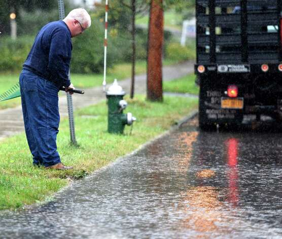 An Albany Department of General Services worker looks for the reason for flooding  Euclid and Western Avenue early Wednesday morning, Sept. 30, 2015, after heavy rainfall in Albany, N.Y. (Skip Dickstein/Times Union) Photo: SKIP DICKSTEIN