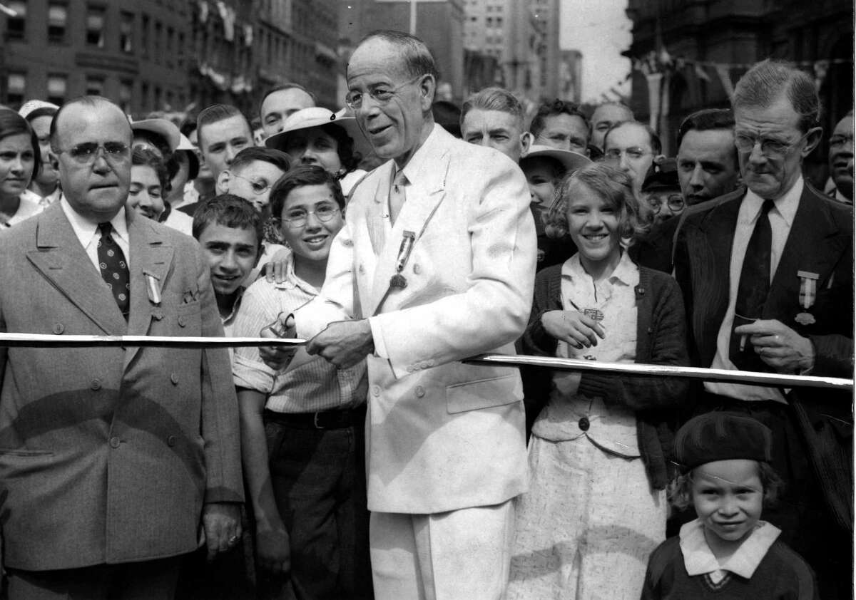 Mayor John Boyd Thacher II, center, cuts a ribbon to commemorate the start Dongan Charter celebration July 22, 1936, in Albany, N.Y. Gilbert P. Venter, city marshal and official., left, and Leo M. Doody, general chairman of the celebration, right. (Times Union archive)