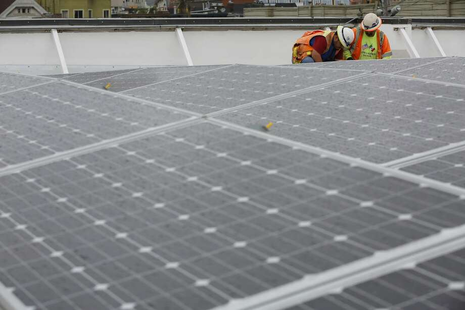 Juan Barraza (left) and Genaro Cornego anchor the seismic system for the solar panels on the roof of Cesar Chavez Elementary School in San Francisco, California, on Wednesday, Sept. 30, 2015. Photo: Connor Radnovich, The Chronicle