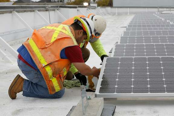 Juan Barraza (front) and Genaro Cornego anchor the seismic system for the solar panels on the roof of Cesar Chavez Elementary School in San Francisco, California, on Wednesday, Sept. 30, 2015.