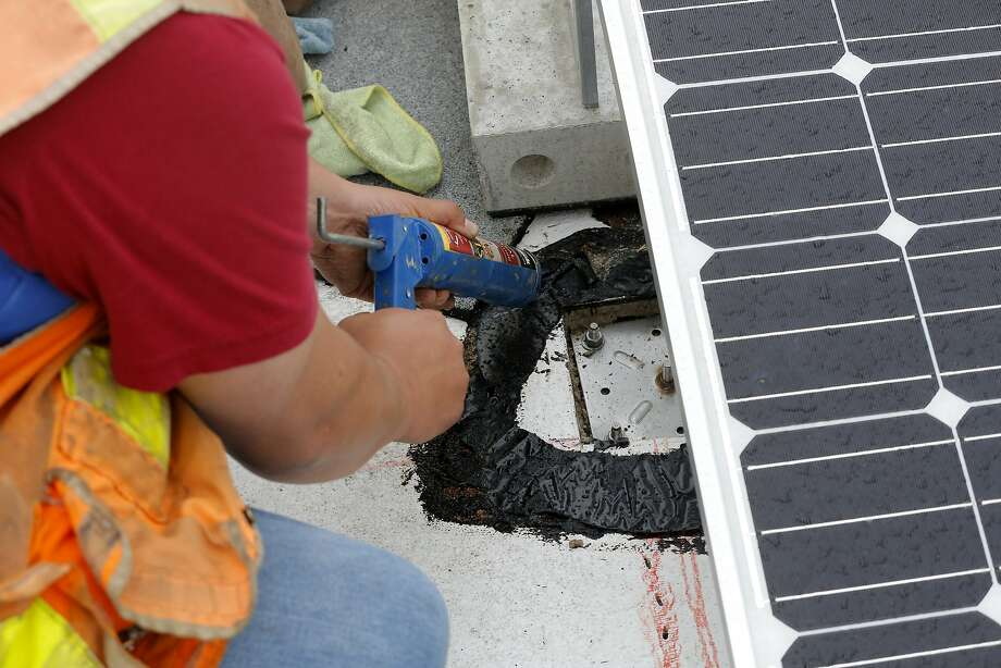 Juan Barraza anchors the seismic system for the solar panels on the roof of Cesar Chavez Elementary School in San Francisco, California, on Wednesday, Sept. 30, 2015. Photo: Connor Radnovich, The Chronicle