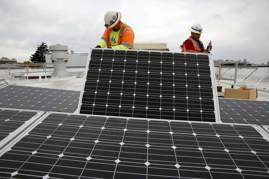 Genaro Cornego (left) and Juan Barraza replace a solar panel on the roof of Cesar Chavez Elementary School in San Francisco, California, on Wednesday, Sept. 30, 2015. Photo: Connor Radnovich, The Chronicle