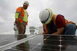 Genaro Cornego (left) and Juan Barraza anchor the seismic system for the solar panels on the roof of Cesar Chavez Elementary School in San Francisco, California, on Wednesday, Sept. 30, 2015.