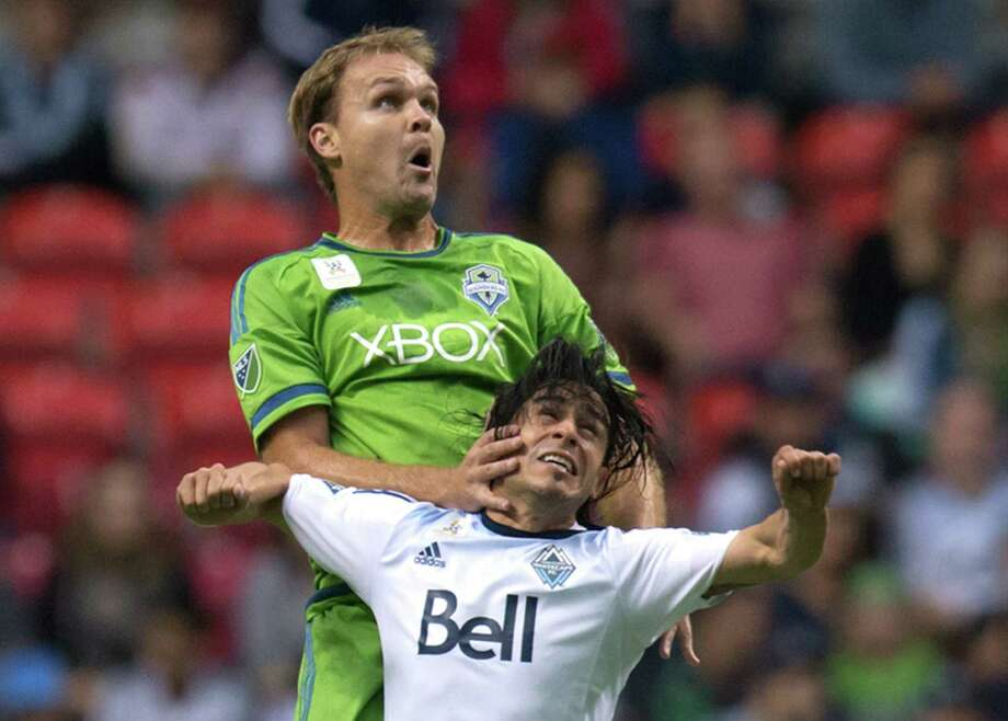 Seattle Sounders' Chad Marshall, back, shoves Vancouver Whitecaps' Mauro Rosales, of Argentina, as they vie for the ball during the first half of an MLS soccer game in Vancouver, British Columbia, on Saturday Sept. 19, 2015. (Darryl Dyck/The Canadian Press via AP) Photo: Darryl Dyck, Associated Press / The Canadian Press
