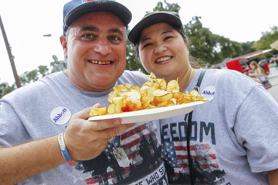 Festival patrons Burt Levine and Sandra Wagar show off their plate of ribbon fries, a popular food at the 2014 Katy Rice Harvest Festival held in downtown Katy. The Katy Rice Harvest Festival comes to town Oct. 10-11 this year. Photo: Diana L. Porter, Freelance / © Diana L. Porter