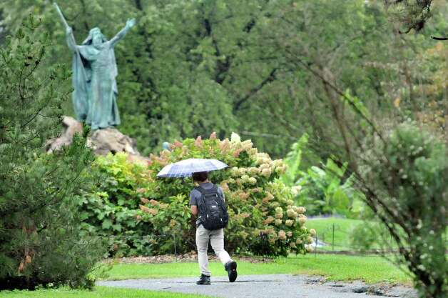 Steven Chuica, 18, of Albany shelters himself from rain on Wednesday, Sept. 30, 2015, at Washington Park in Albany, N.Y. (Cindy Schultz / Times Union) Photo: Cindy Schultz / 10033561A
