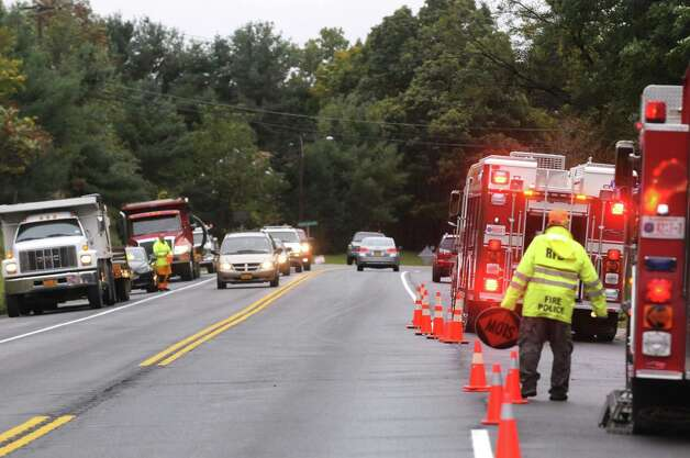 Fire police keep traffic moving along Route 7 as crews rebuild a road washed away during flooding on Terrace Drive the entrance off of Rout 7 to Terrace Haven Community a mobile home park on Wednesday Sept. 30, 2015 in Brunswick , N.Y.  (Michael P. Farrell/Times Union) Photo: Michael P. Farrell / 10033570A