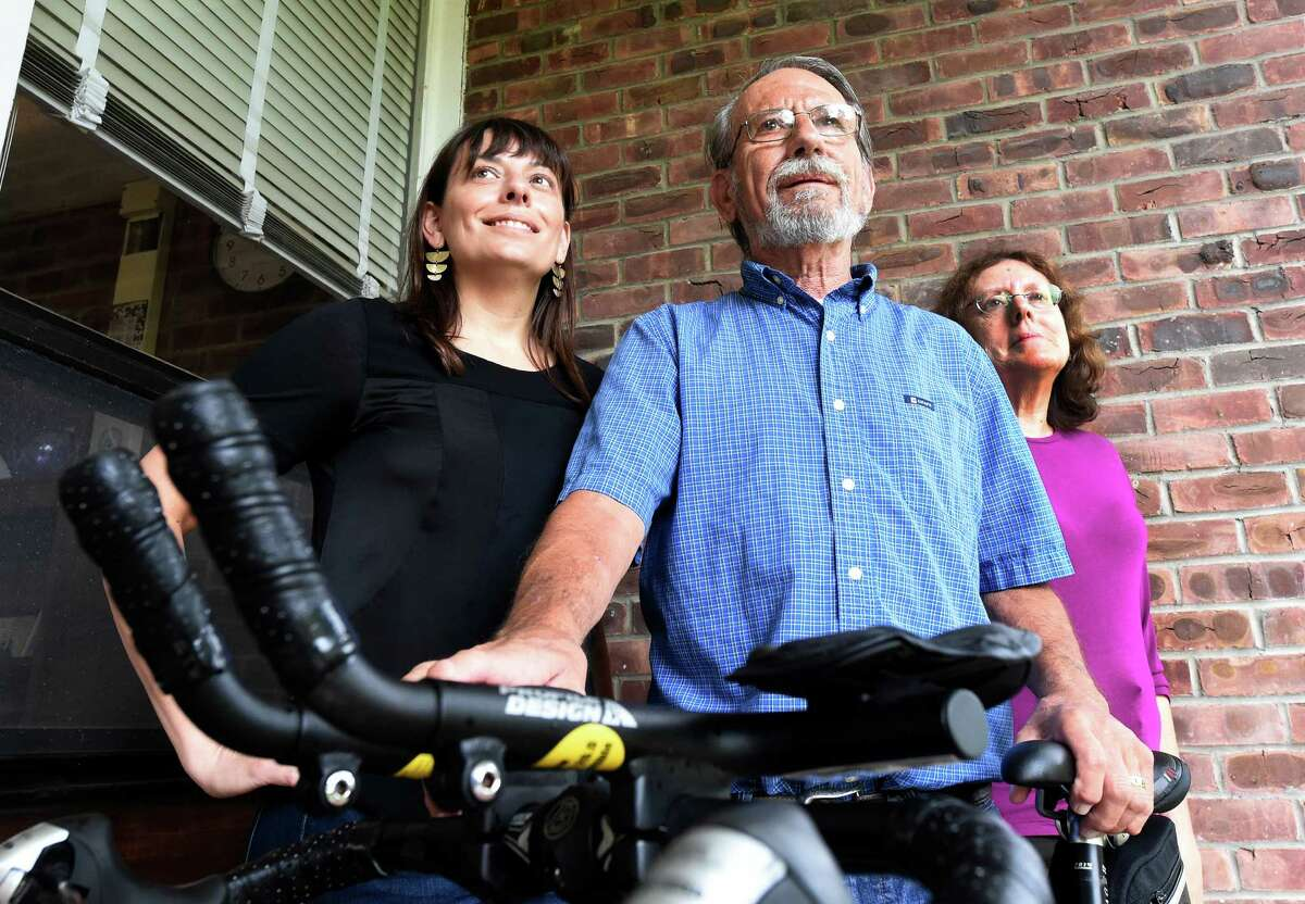 The Strope family, Sara, left, Harold and Miriam stand near Harold's bike at the Albany Academy for Girls Sept. 30, 2015 in Albany, N.Y. On Thursday, October 1st, Sara Strope and her father will embark on a four-day, 200-mile bike ride, departing from Delmar. In 1995, during Sara's senior year at Albany Academy for Girls, her father had lifesaving surgery at Mass General in Boston - a heart transplant. Now they are embarking on this ride together celebrate the 20th anniversary of his transplant. They will be biking the route that Harold Strope took 20 years ago to receive his heart. They will be gathering at 9:00am Thursday at the Seville Bike Shop in Delmar to leave at 9:30. At least a dozen community members will be gathering to send them off. (Skip Dickstein/Times Union)