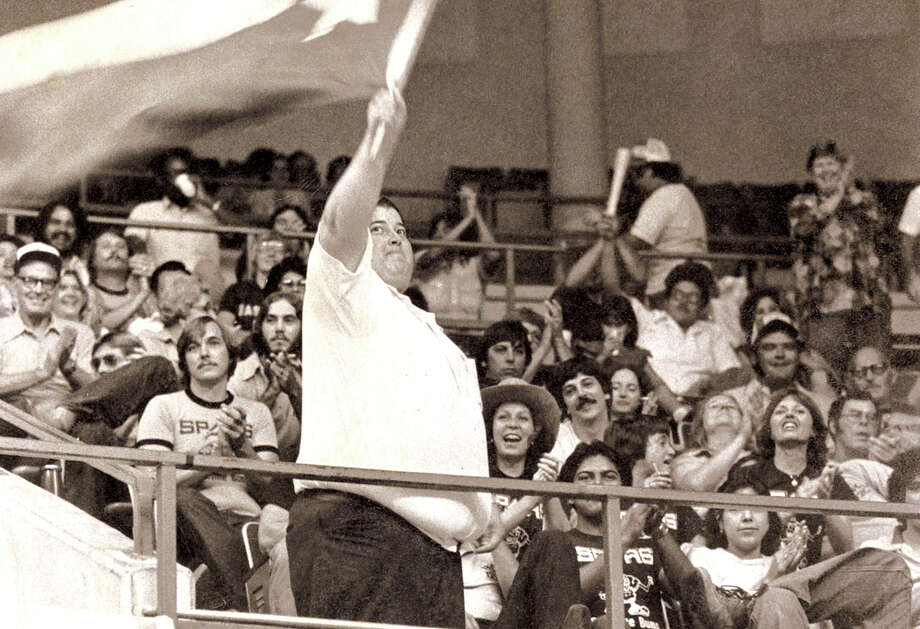 George Valle, the enthusiastic leader of the Spurs' Baseline Bums, waves a Texas flag at a 1980 game at HemisFair Arena. Photo: File Photo