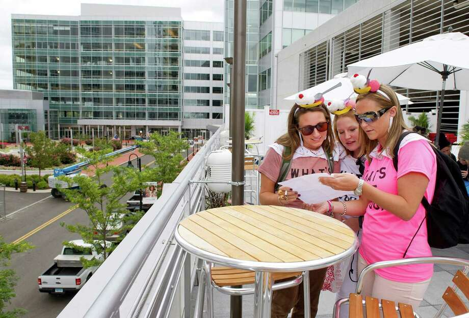 From left, Stefanie Suppa, Maureen Mehner and Kerilyn Whitehead look over the clues during last year's Urban Scavenger Race at Sign of the Whale at Harbor Point. Photo: Lindsay Perry / Hearst Connecticut Media / Stamford Advocate