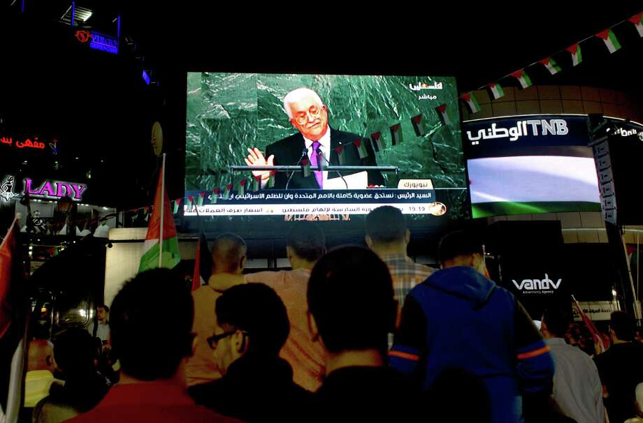 Palestinians watch a speech by Palestinian President Mahmoud Abbas at the U.N. General Assembly shown on TV in the West Bank city of Ramallah, Wednesday, Sept. 30, 2015. Abbas declared before world leaders Wednesday that he is no longer bound by agreements signed with Israel, and called on the United Nations to provide international protection for the Palestinian people. (AP Photo/Nasser Nasser) Photo: Nasser Nasser, STF / AP