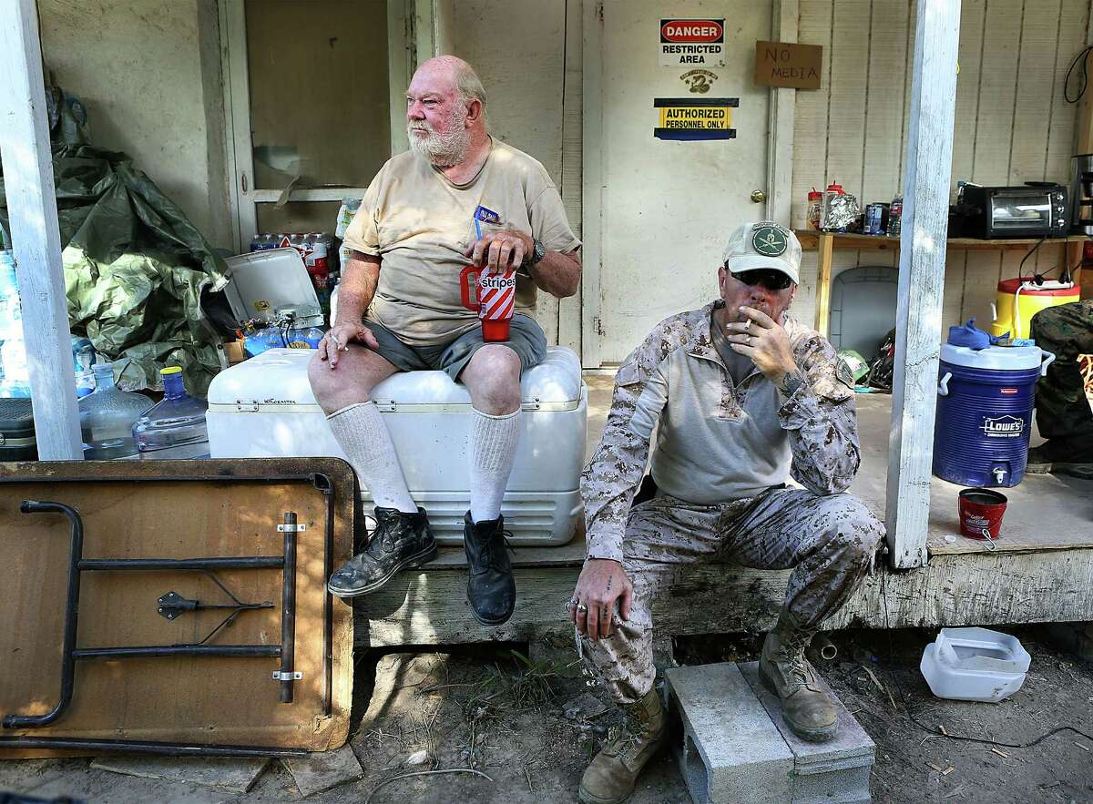 KC Massey, right, takes a drag on a cigarette as he sits with land owner Rusty Monsees Jr. Monsees asked the militia group called Camp Lone Star, to set up camp on his property along the Rio Grande River in Brownsville, TX. Wednesday, September 10, 2014