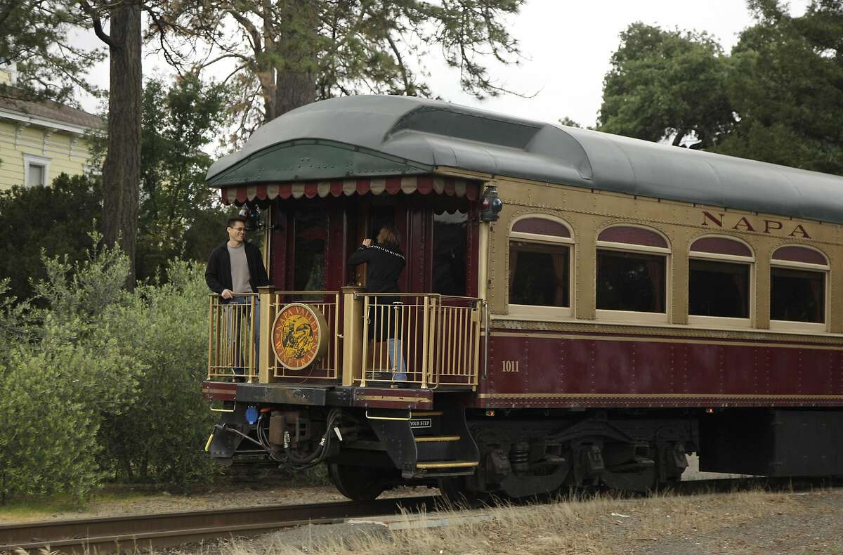 In this June 2, 2011 file photo, a couple takes pictures at the back of the Napa Valley Wine Train as it makes its way through St. Helena, Calif. Members of a mostly black book club say they believe they were kicked off the train because of their race. The women say they were ordered off the wine train Saturday, Aug. 22, 2015. Book club member Lisa Renee Johnson said that employees told the women they were laughing and talking too loudly. (AP Photo/Eric Risberg, File)