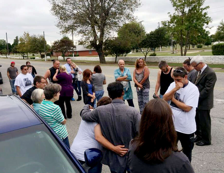 Family members of Richard Glossip and others opposed to Glossip's execution bow their heads outside the Oklahoma State Penitentiary in McAlester, Okla., on Wednesday, Sept. 30, 2015, shortly after learning Glossip's appeal had been denied by the U.S. Supreme Court. Gov. Mary Fallin has granted a last-minute stay saying the state needed to determine whether its use of a new drug, potassium acetate, was in compliance. (David Dishman/McAlester News Capital via AP) Photo: David Dishman, MBR / McAlester News Capital