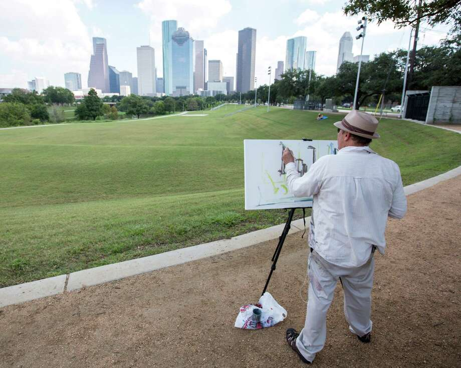 Arthur Deatly paints the city skyline from Eleanor Tinsley Park in the renewed Buffalo Bayou area. Photo: Jon Shapley, Staff / © 2015 Houston Chronicle