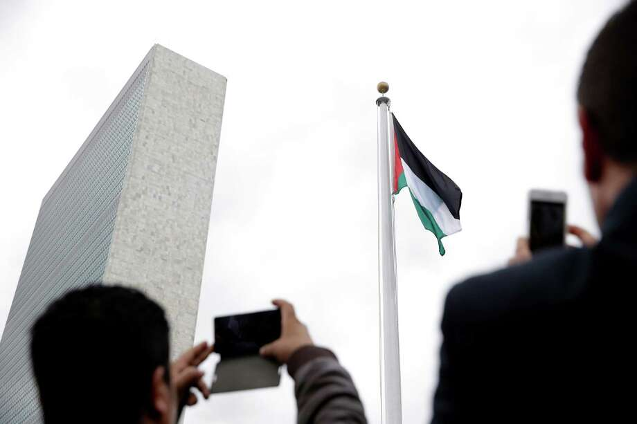 People photograph the State of Palestine flag as it flies for the first time at U.N. headquarters, Wednesday, Sept. 30, 2015. (AP Photo/Seth Wenig) ORG XMIT: UNSW121 Photo: Seth Wenig / AP