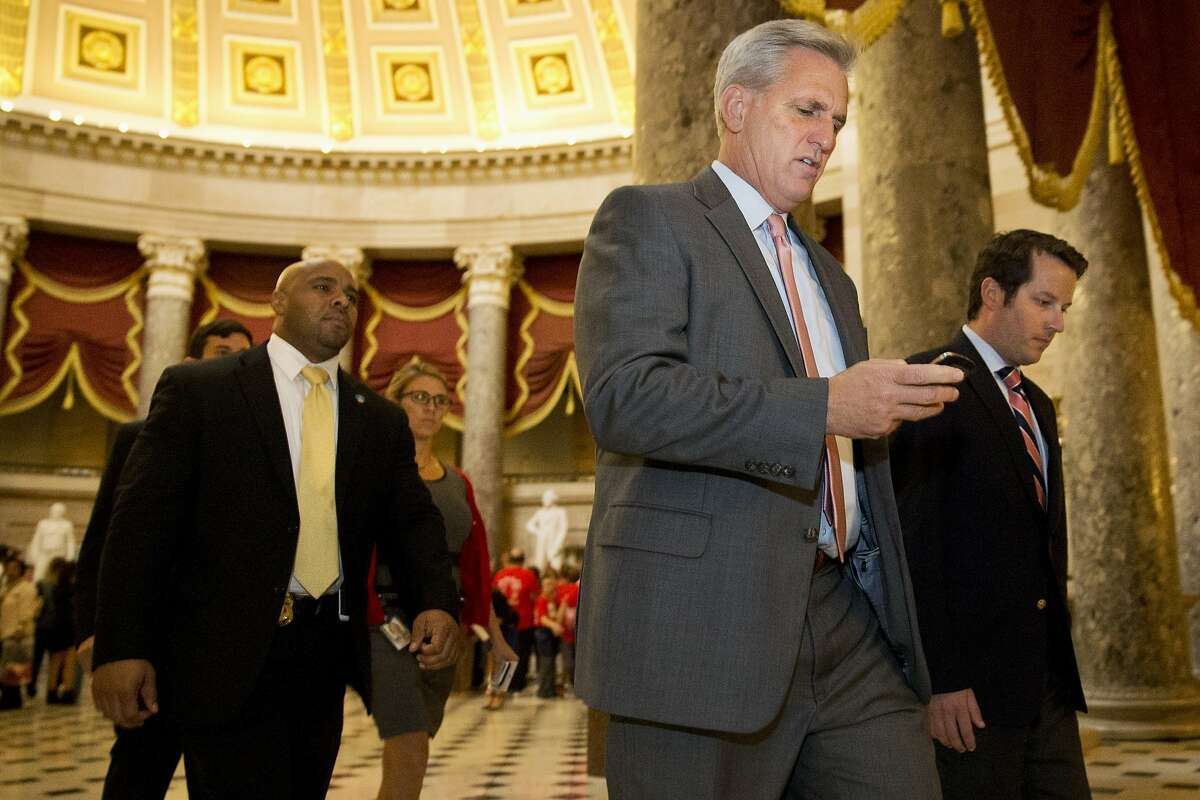 House Majority Leader Kevin McCarthy of Calif., center, walks to a procedural vote and debate in the House on a stopgap spending bill to avert a government shutdown, Wednesday, Sept. 30, 2015, on Capitol Hill in Washington. A temporary funding measure aiming to keep the government open past a midnight deadline sailed through the Senate on Wednesday and was expected to make its way shortly through a divided House and on to President Barack Obama. (AP Photo/Jacquelyn Martin)