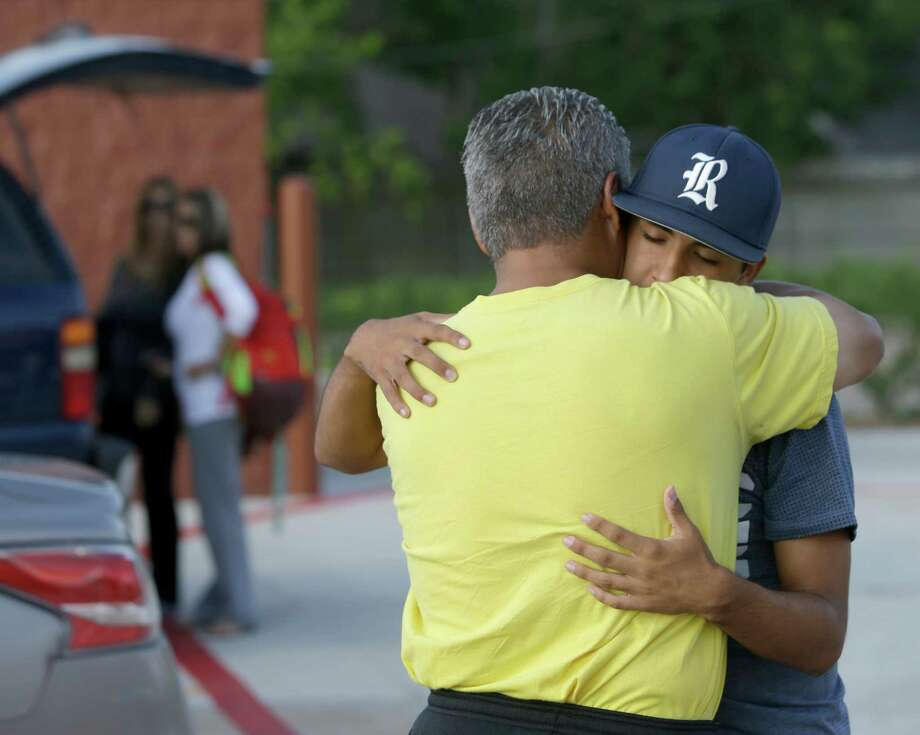 Dalton Herrera, 15, and his father, Val Herrera, hug for the first time in months Wednesday in Pasadena. His mother, Michelle Herrera, and her twin sister, Lisa Baylor, left, watch nearby. Photo: Melissa Phillip, Staff / © 2015 Houston Chronicle