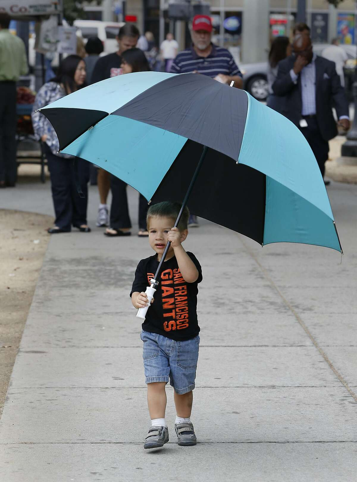 With umbrella in hand Silas Brownsey, 2, came prepared for rain that fell during his visit to a farmers market in downtown Sacramento, Calif., Wednesday, Sept. 30, 2015. The brief rain fall, while welcome, brought little relief from California's four-year-old drought .(AP Photo/Rich Pedroncelli)