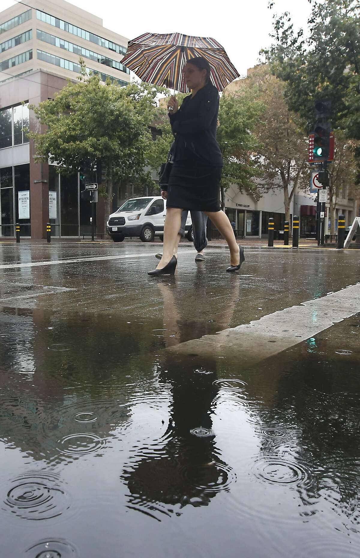 An umbrella is reflected in the pool of rain water on 10th St. in downtown, Sacramento, Calif., Wednesday, Sept. 30, 2015. The brief rain fall, while welcome, brought little relief from California's four-year-old drought .(AP Photo/Rich Pedroncelli)