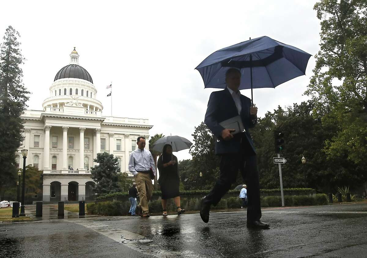 Umbrellas came into use as a brief storm brought the first few rain drops of autumn to Sacramento Calif., Wednesday, Sept. 30, 2015. The brief rain fall, while welcome, brought little relief from California's four-year-old drought.(AP Photo/Rich Pedroncelli)