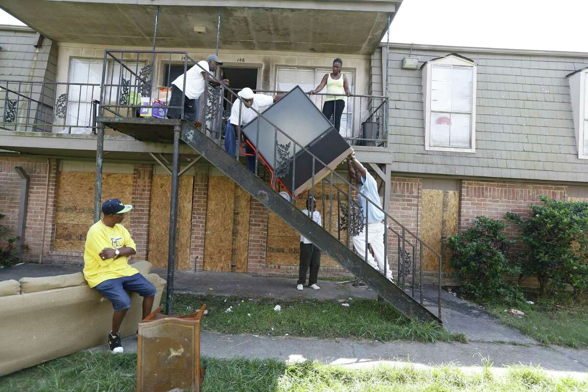 Kenneth Ray Harris, top of stairs, left, moves a TV at Crestmont Village. He is putting items into storage while he seeks a home.
