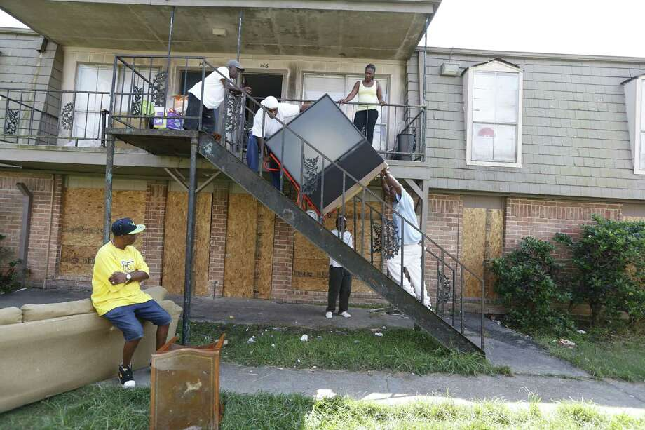 Kenneth Ray Harris, top of stairs, left,  moves a TV at Crestmont Village. He  is putting items into storage while he seeks a home.  Photo: Steve Gonzales, Staff / © 2015 Houston Chronicle