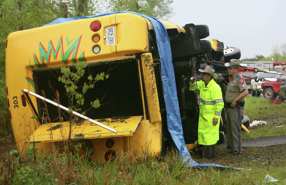 State troopers in 2006 analyze a mini-bus  after it rolled over in an accident on U.S. 290, killing  two students and injuring the remaining 22.