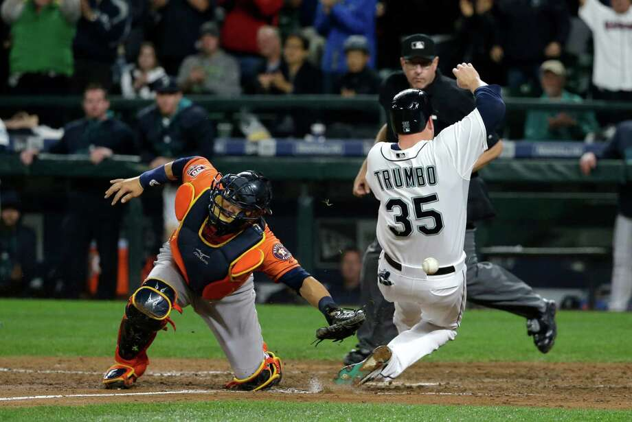 Seattle Mariners' Mark Trumbo (35) scores on a single hit by Mariners' Shawn O'Malley as Houston Astros catcher Hank Conger is unable to get to the throw in the eighth inning of a baseball game Tuesday, Sept. 29, 2015, in Seattle. (AP Photo/Ted S. Warren) Photo: Ted S. Warren, STF / AP