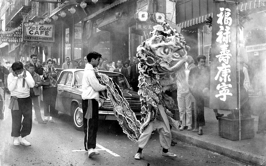Feb. 16, 1964: A lion dancer can be seen in the haze of fireworks in San Francisco's Chinatown. Photo: Gordon Peters, The Chronicle