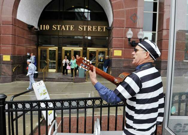 Members of the Prison Blues Brothers, Andres Rieloff, foreground and Randy Credico, background, dressed in prison stripes, stage a protest outside the State Comptroller's office on Wednesday, Sept. 30, 2015, in Albany, N.Y.  The two men with the group, End the Prison Industrial Complex Now, were calling on Comptroller Tom DiNapoli to end the use of New York pension fund money to support the private prison industry.  (Paul Buckowski / Times Union) Photo: PAUL BUCKOWSKI / 10033562A