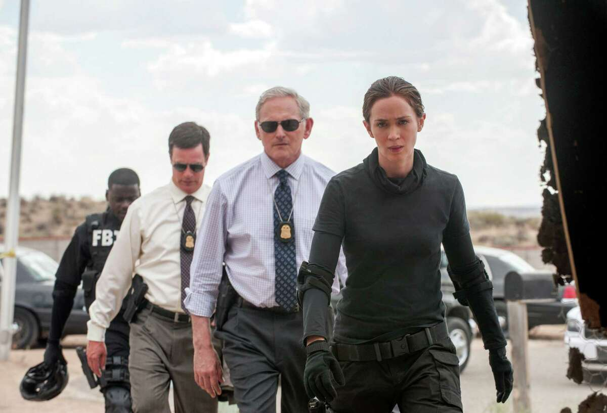 This photo provided by Lionsgate shows, Daniel Kaluuya, from rear left, as Reggie Wayne, Phil Coopers as Hank Rogerson, Victor Garber as Dave Jennings, and Emily Blunt, as Kate Macer, in a scene from the film,