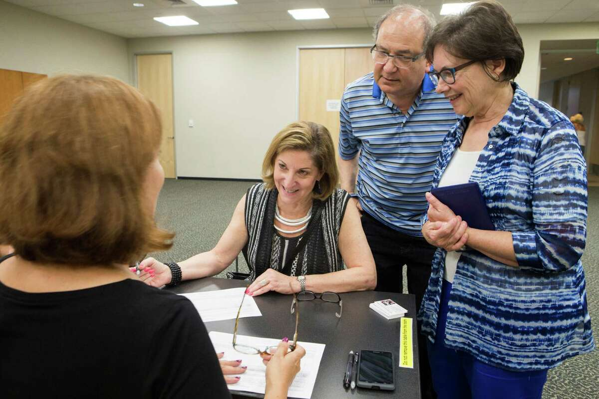 Ann Magoon, center, a neighbor of Sugar Land listens to the referendum petition to rescind Ordinance 2014 before signing it accompanied by Judy Lusky and her husband Mal Lusky, Monday, Sept. 21, 2015, in Sugar Land. ( Marie D. De Jesus / Houston Chronicle )