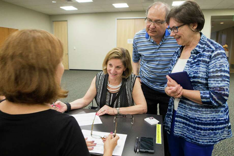 Ann Magoon, center, a neighbor of Sugar Land listens to the referendum petition to rescind Ordinance 2014 before signing it accompanied by Judy Lusky and her husband Mal Lusky, Monday, Sept. 21, 2015, in Sugar Land. ( Marie D. De Jesus / Houston Chronicle ) Photo: Marie D. De Jesus, Staff / © 2015 Houston Chronicle