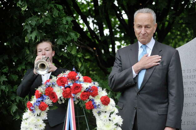 Kelly Streznewski, left, a member of the Albany Marching Falcons and a student at Albany High School, plays taps as Senator Charles Schumer looks on at the Henry Johnson memorial in Washington Park on Sunday, May 31, 2015, in Albany, N.Y.  On Tuesday President Barack Obama will award the Medal of Honor to Johnson for his heroism in World War I in France.  (Paul Buckowski / Times Union) Photo: PAUL BUCKOWSKI / 00032086A