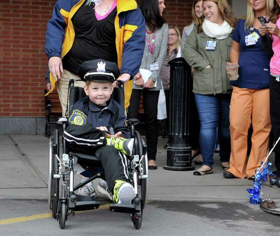 Evan Borggreen, 4, of Unadilla, is wheeled out by his mom, Theresa, outside of Albany Med on Thursday, Oct. 1, 2015, in Albany, N.Y.  Borggreen is  battling acute lymphoblastic leukemia and is being treated at the Bernard & Millie Duker Children's Hospital at Albany Medical Center.  Borggreen was sworn in as an honorary police officer in front of numerous members of the Albany Police force.  One of Borggreen's nurses, R.N. Ellen Scheer, knew that he wanted to be a police officer when he grows up and Borggreen has even made it a habit of going around to check in on other children in the hospital.  Scheer contacted Albany Police officer Christopher McCoy who talked to his command officers and city hall to make the event happen.  (Paul Buckowski / Times Union) Photo: PAUL BUCKOWSKI / 10033565A
