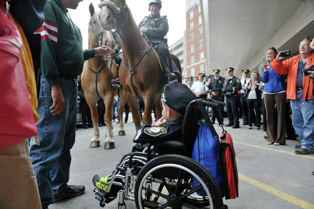 Evan Borggreen, 4, of Unadilla, looks up at the Albany Police mounted patrol officers outside of Albany Med on Thursday, Oct. 1, 2015, in Albany, N.Y.  Borggreen was sworn in as an honorary police officer in front of numerous members of the Albany Police force.  Borggreen is  battling acute lymphoblastic leukemia and is being treated at the Bernard & Millie Duker Children's Hospital at Albany Medical Center. One of Borggreen's nurses, R.N. Ellen Scheer, knew that he wanted to be a police officer when he grows up and Borggreen has even made it a habit of going around to check in on other children in the hospital.  Scheer contacted Albany Police officer Christopher McCoy who talked to his command officers and city hall to make the event happen.  (Paul Buckowski / Times Union) Photo: PAUL BUCKOWSKI / 10033565A