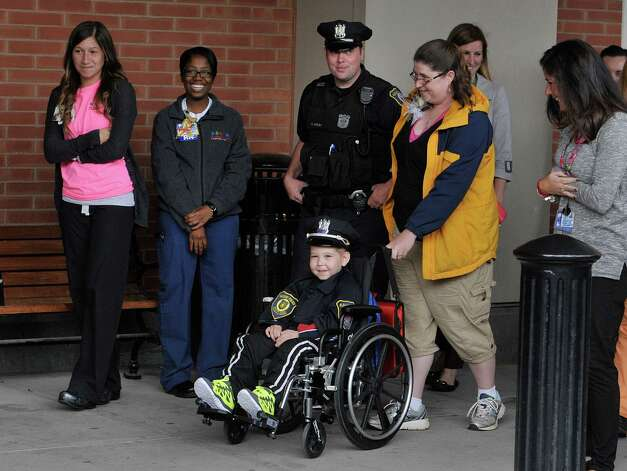Evan Borggreen, 4, of Unadilla, is wheeled out by his mom, Theresa and accompanied by Albany Police officer Christopher McCoy outside of Albany Med on Thursday, Oct. 1, 2015, in Albany, N.Y.   Borggreen is  battling acute lymphoblastic leukemia and is being treated at the Bernard & Millie Duker Children's Hospital at Albany Medical Center.  Borggreen was sworn in as an honorary police officer in front of numerous members of the Albany Police force.  One of Borggreen's nurses, R.N. Ellen Scheer, knew that he wanted to be a police officer when he grows up and Borggreen has even made it a habit of going around to check in on other children in the hospital.  Scheer contacted Albany Police officer Christopher McCoy who talked to his command officers and city hall to make the event happen.  (Paul Buckowski / Times Union) Photo: PAUL BUCKOWSKI / 10033565A