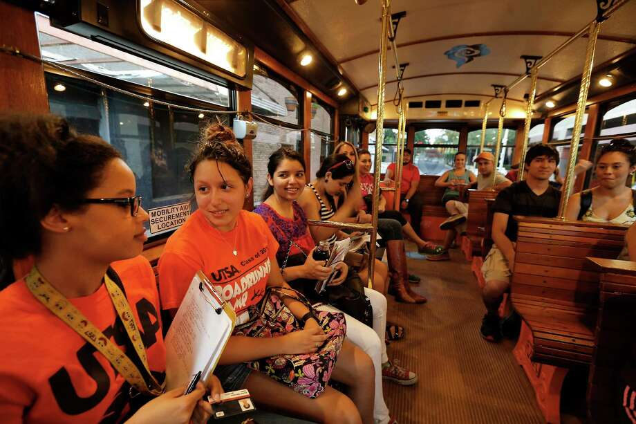 UTSA students Krystyn Malveaux (left) and Kayla Sanchez ride   on the VIA downtown circulator called The E for an art class visiting art installations near the HemisFair on Wednesday. Photo: Kin Man Hui / San Antonio Express-News / ©2015 San Antonio Express-News