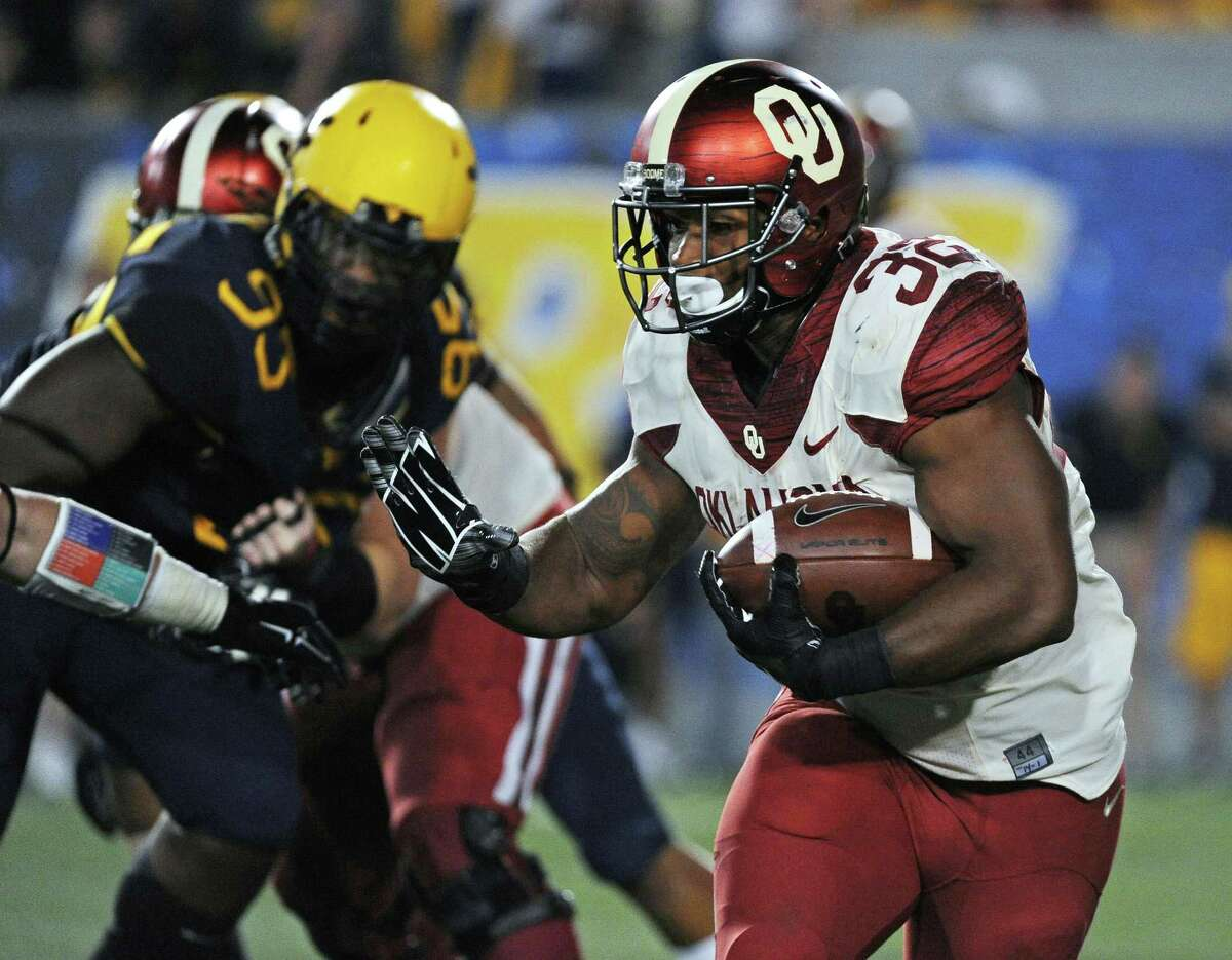 Oklahoma's Samaje Perine (32) reaches to stiff-arm a West Virginia defender during the fourth quarter of an NCAA college football game in Morgantown, W.Va. Oklahoma's Samaje Perine rattles teeth, opens eyes and plants bad memories in would-be tacklers who are left adjusting their helmets and soothing aching muscles. Perine did all that a year ago against West Virginia, when the 243-pound tank ran for 242 yards and scored four touchdowns against the Mountaineers. On Saturday, West Virginia defenders are expecting more of the same punishment while trying to limit Perine's output when the 15th-ranked Sooners and 23rd-ranked Mountaineers meet in Norman, Oklahoma.